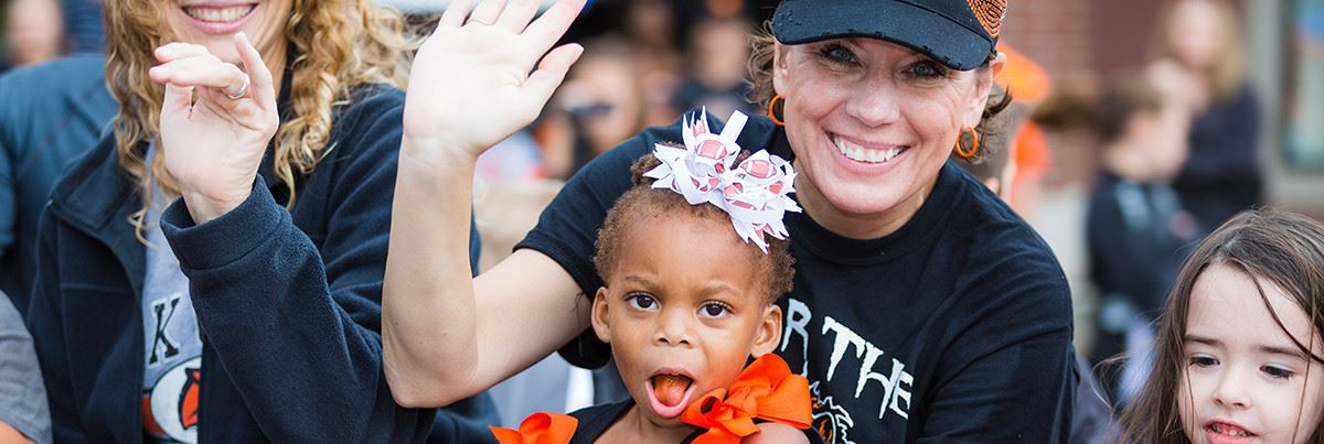 Woman holding young girl at football game